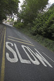 Danger ahead!. Road safety measure; SLOW painted across road warning / asking drivers to take care royalty free stock photo