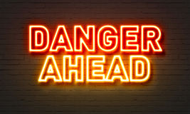 Danger ahead neon sign on brick wall background. Danger ahead neon sign on brick wall background royalty free stock images