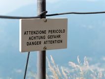 Danger Attention translation signpost or signboard mountain environment. Danger Attention translation signpost mountain environment Royalty Free Stock Photos