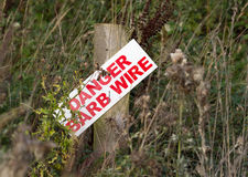 Danger barb wire sign on post Royalty Free Stock Photos