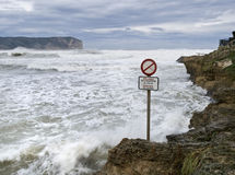 Danger in the Beach. Image of the stormy sea with a signal of danger on the foreground Royalty Free Stock Image
