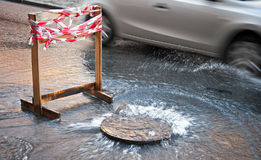 Danger border near water leak. On the road Royalty Free Stock Photography