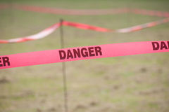 Danger Boundary Tape in a Field. Stock Photo