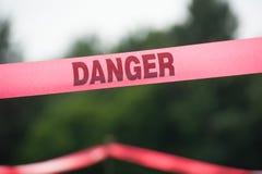 Danger Boundary Tape in a Field. Pink danger boundary tape in a field Royalty Free Stock Photos
