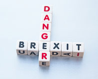 Danger Brexit. Small white cubes arranged crossword style spelling danger vertically and brexit horizontally, silver background. Concept of danger of Britain Stock Photos