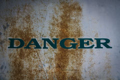 Danger caution on rusty metal wall. Stock Photo