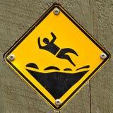 Danger : chute sur le signe extérieur rocheux photographie stock