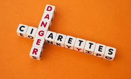 Danger cigarettes. Text ' danger ' and ' cigarettes ' in uppercase letters inscribed on small white cubes arranged crossword style with common letter ' g ' Stock Photos