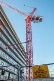Danger construction site keep out sign with red crane over city. Office block. Dangerous inner-city building work Royalty Free Stock Photos