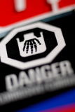 Danger Corrosive Label - Skeletal Hand. Danger, Corrosive label with Skeletal Hand symbol. Black label with white symbol and text. Some red and blue. Shallow DOF Royalty Free Stock Photos