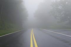 Danger de route disparaissant dans le brouillard Photos stock