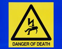 Danger of death from electricity sign on blue background Royalty Free Stock Images