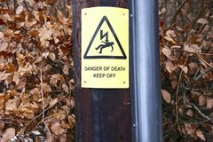 Danger of death keep off yellow sign post. Against brown hedge in wilderness countryside Stock Photography
