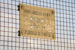 Danger of death sign on a railway fence bridge. Danger of death sign on an italian railway fence bridge, don`t touch wires italian language Stock Images