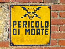 Danger of death signs with skull and crossbones written in Itali Royalty Free Stock Image
