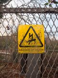Danger of death yellow rusty dirty unclean sign on metal fence l Stock Photos