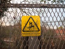 Danger of death yellow rusty dirty unclean sign on metal fence l Stock Photography