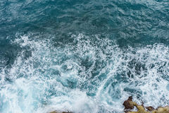 Danger deep blue ocean with wave crashing on rock coast with spr. Ay and foam aerial view Stock Images