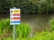 Danger Deep Water No Swimming. Danger notice on the bank of a lake warning the public about deep water and forbidding swimming Stock Image
