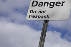 Danger Do Not Trespass Sign. With blue cloudy sky background in Houston, British Columbia, Canada stock image