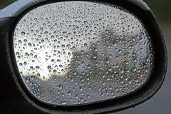 Danger when driving. Photo of a car wing mirror with rain on it making it a driving hazard royalty free stock image