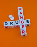 Danger drugs. Text ' danger ' and ' drugs ' inscribed in uppercase letters on small white cubes and arranged crossword style with common letter ' g ', orange Royalty Free Stock Photos
