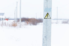 Danger Electrical Hazard High Voltage Sign. Winter nature on background stock photo