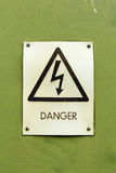 Danger electricity sign on a green background Royalty Free Stock Photography