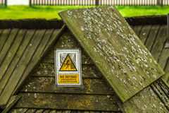 Danger electricity. Sign Danger High Voltage Electricity on an old wooden housing Stock Images