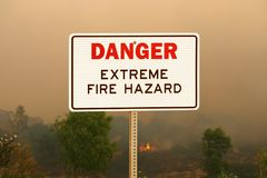 Danger Extreme Fire HazardSign with Wildfire Background. Danger extreme fire hazard sign with wildfire background stock photography