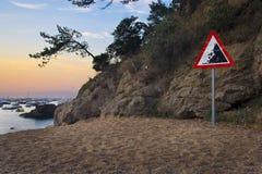 Danger falling rocks sign on Mediterranean beach Royalty Free Stock Image