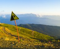 The danger of falling warning sign on a steep mountain side stock photography