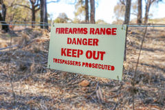 Danger Firearms Range Keep Out Trespassers Prosecuted sign on fence Royalty Free Stock Image