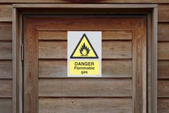 Danger flammable gas warning caution sign on wooden door. At boiler plant room Royalty Free Stock Photos
