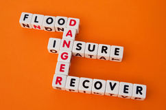 Danger of flooding. Text ' flood ', ' danger ' , ' insure ' and ' recover ' inscribed in uppercase letters on small cubes and arranged crossword style with Stock Photo
