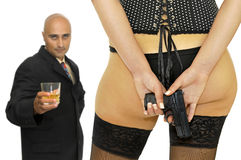 Danger girl. Woman hiding a gun from a businessman, isolated in white Royalty Free Stock Images