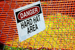Danger Hart Hat Area Sign in Construction Zone. Danger hard hat area safety warning sign on a chain link fence in a work site construction zone royalty free stock photo