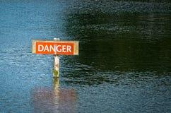 Danger Hazard Warning Sign in River. Red danger hazard warning sign in the middle of a river royalty free stock photography