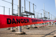 Danger high voltage. Red danger tape barricade for high voltage safety with switchyard at the background royalty free stock image