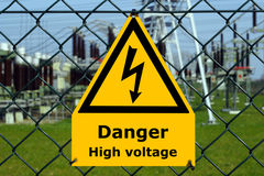 Danger! High Voltage - English. USA high voltage sign with substation, blue sky and green grass in the background Royalty Free Stock Image