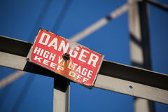 Danger high voltage keep off sign. Red sign warning to keep off of power tower with dangerous electricity. Do not enter may cause shock emergency Stock Image