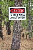 Danger Impact Area Do Not Enter Warning Sign Post. On a pine tree at a military installation shooting and firing training range on an army base to prevent Stock Images