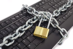 Danger in internet. Locked chain on computer keyboard as sybol for danger in internet Stock Photo