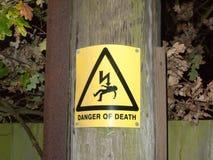 Danger jaune de signe de sécurité de la mort en dehors de shoc de l'électricité de poteau Images libres de droits