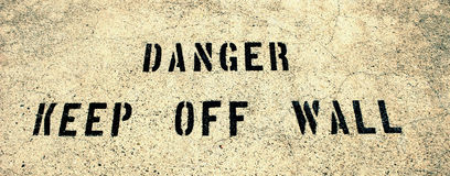 Danger keep off wall. Warning sign enscribed on the steep walls of Hoover Dam Royalty Free Stock Photography