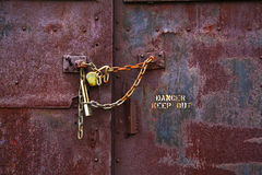 Danger Keep Out. Detail of lock and chain on rusted door with warning sign royalty free stock photo
