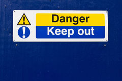 Danger keep out sign. Yellow and blue danger keep out sign on wall royalty free stock photography