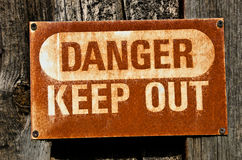 Danger Keep Out Sign. Rusty, old sign warning of danger and telling us to keep out royalty free stock photo