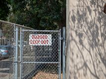 Danger keep out sign behind a residential chain link fence in residential area stock image