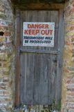 Danger keep out. Sign on an old wooden door stock photo